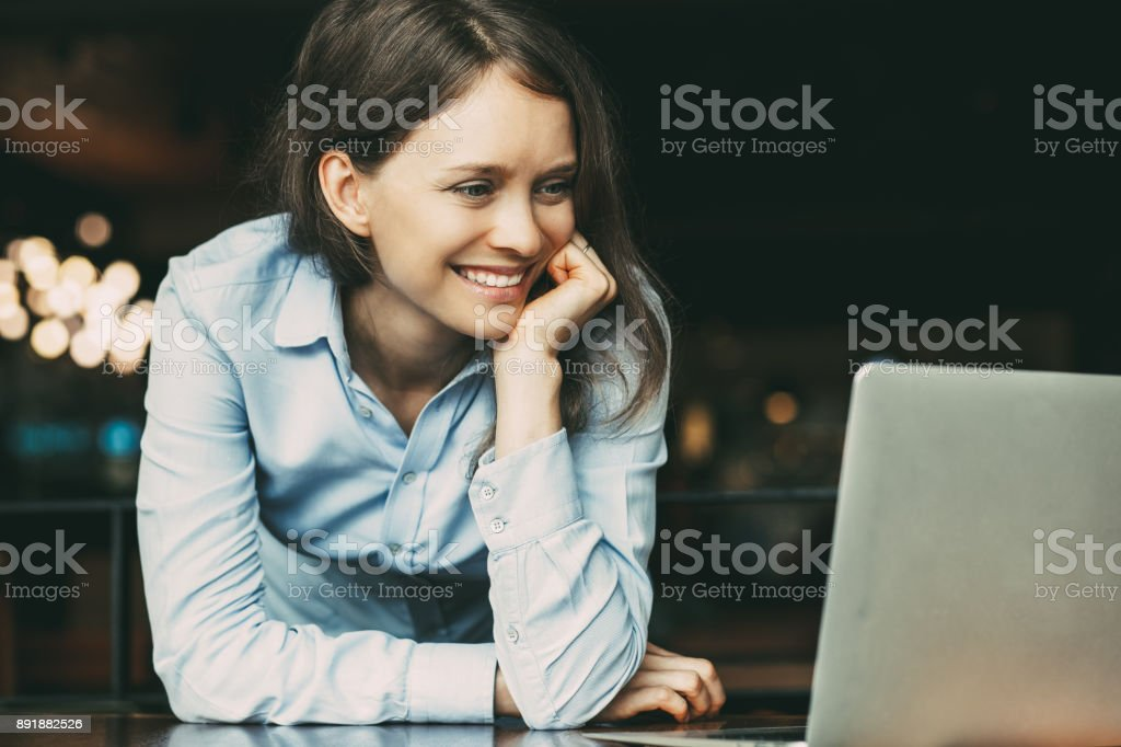 Positive young woman using laptop at table_tone stock photo
