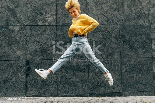 870648602 istock photo Positive young woman wearing yellow sweater, blue hight waist jeans, jumping high, feeling happy on the city street. Student blonde female as joyful expression 1208329590