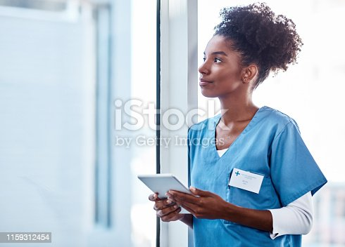 Shot of a young doctor using a digital tablet in a hospital and looking away thoughtfully