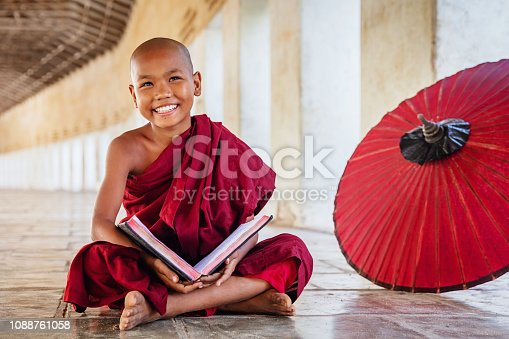 Happy smiling burmese buddhist novice monk sitting on the floor of an archway of buddhist monastery, holding and reading a book, looking up with a bright happy confident smile. Real People. Old Bagan, Mandalay Region, Myanmar.