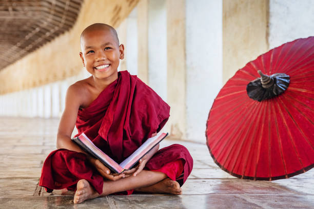 Positivity Novice Monk in Monastery Archway, Myanmar Happy smiling burmese buddhist novice monk sitting on the floor of an archway of buddhist monastery, holding and reading a book, looking up with a bright happy confident smile. Real People. Old Bagan, Mandalay Region, Myanmar. myanmar stock pictures, royalty-free photos & images