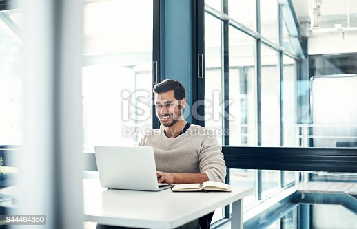 Shot of a young businessman using a laptop at his desk in a modern office