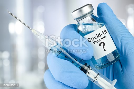 Possible cure concept with a hand in blue medical gloves holding Coronavirus, Covid 19 virus, vaccine vial