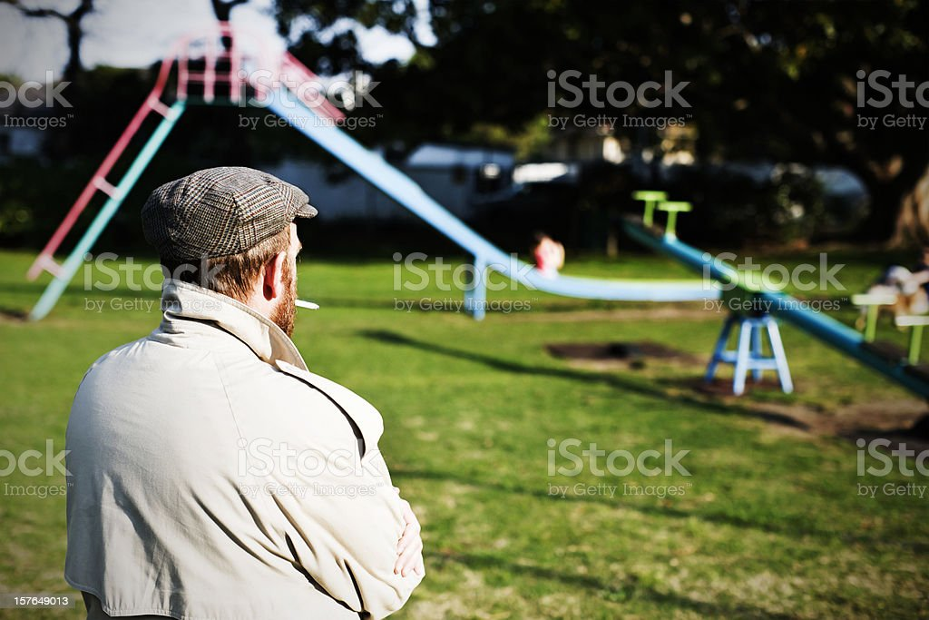 Possible pedophile watches a children's playground for potential prey stock photo