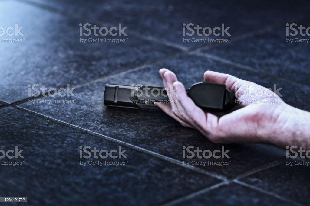 Possible suicide: dead man's hand on floor holding pistol stock photo