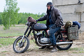 istock A post apocalyptic man on motorcycle near the destroyed building 967125014