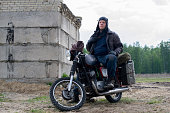 istock A post apocalyptic man on motorcycle near the destroyed building 967125472