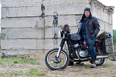 istock A post apocalyptic man on motorcycle near the destroyed building 967125744