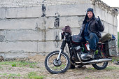 istock A post apocalyptic man on motorcycle near the destroyed building 967133200