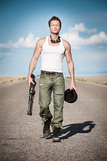 Post Apocalyptic Warrior Fit young man with modified shot gun walks determinedly along a deserted roadway in desolate wasteland. adversarial stock pictures, royalty-free photos & images
