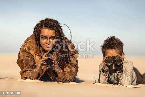 istock Post apocalyptic Woman and Boy Outdoors in a Wasteland 1191851313