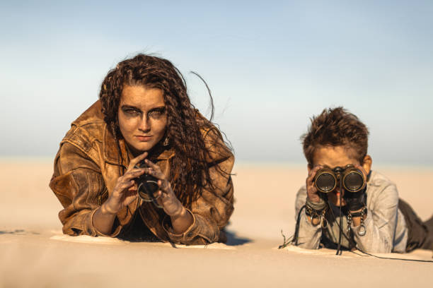 Post apocalyptic Woman and Boy Outdoors in a Wasteland Post apocalyptic woman and boy with binoculars outdoors. Desert and dead wasteland on the background. Aggressive girl warrior in shabby clothes and young boy laying a sand in ambush watching someone to attack and rob. People in nuclear post-apocalypse time. Life after doomsday concept. ambush stock pictures, royalty-free photos & images