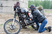 istock A post apocalyptic woman near motorcycle near the destroyed building 967130412
