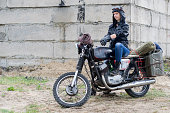 istock A post apocalyptic woman on motorcycle near the destroyed building 967129082