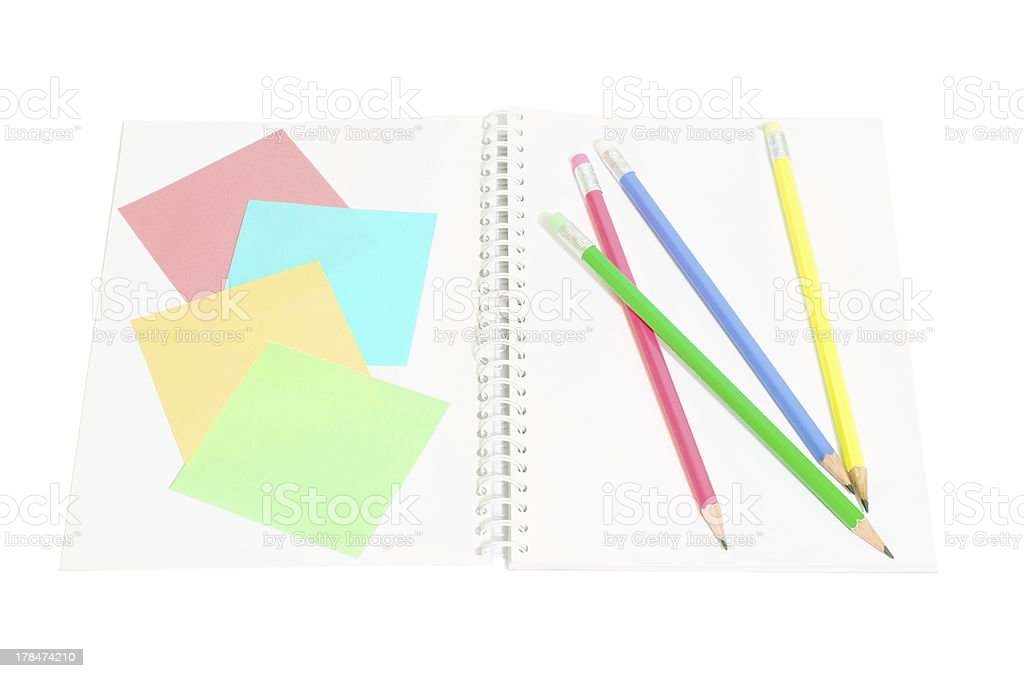 Post it paper and colored pencils on a notebook royalty-free stock photo