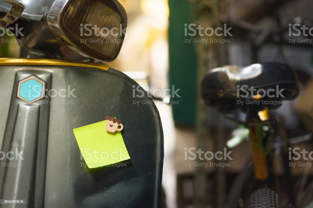 Post note paper sheet or sticky sticker on the scooter with blur old bicycle background, stock photo