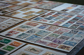 Woman watching postage stamps isolated