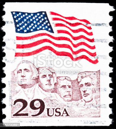 Royalty free stock photo of US postage stamp. It represents the American flag waving  above Mt. Rushmore featured on a 29-cent stamp.