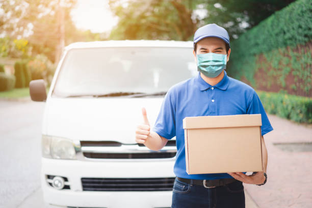 Postal delivery courier man thumbs up wearing protective face mask in front of cargo van delivering package holding box due to Coronavirus disease or COVID-19 outbreak situation in all of landmass in the world.