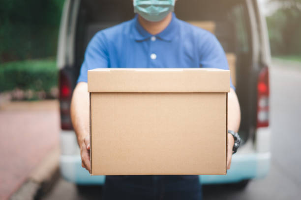Postal delivery courier man wearing protective face mask in back of cargo van delivering package holding box due to Coronavirus disease or COVID-19 outbreak situation in all of landmass in the world.