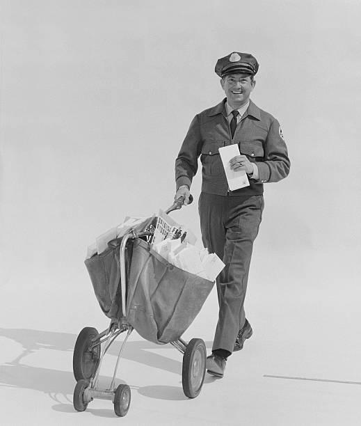 почтовый работник нести букв на колесо против белых bac barrow - postal worker стоковые фото и изображения