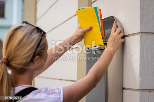 497101689istockphoto Postal worker is inserting letters into mailbox. 1167649754