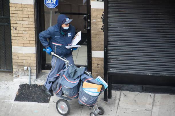 postal worker making deliveries during covid-19 pandemic - postal worker стоковые фото и изображения