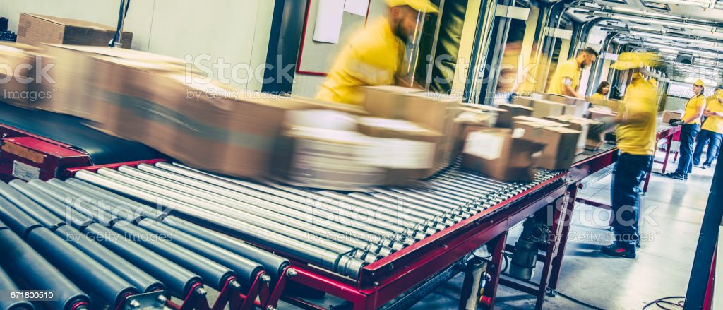 Postal workers inspecting packages on a conveyor belt stock photo