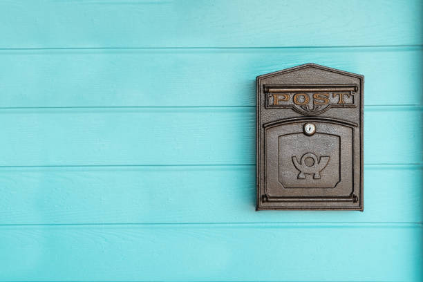 postbox hanging on a blue wood wall stock photo