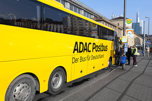 ADAC Postbus Frankfurt, Germany - January 30, 2014: Sideview of ADAC Postbus in the city center of Frankfurt, in the background some boarding passengers. ADAC Postbus is an Intercity bus service of Deutsche Post Mobility and German automobile association ADAC. It operates after the deregulation of the German Fernbusverkehr (intercity bus connections) various routes through Germany. deregulation stock pictures, royalty-free photos & images