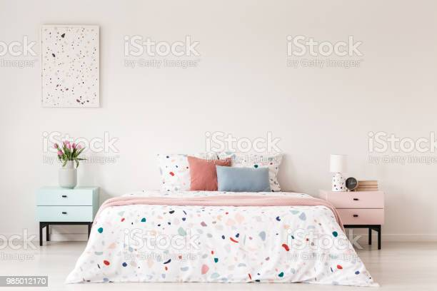 Poster above cabinet with flowers next to bed with colorful pillows picture id985012170?b=1&k=6&m=985012170&s=612x612&h=xoo0uiurloxn ukxkbnrtdbrbyh4ttmuipvlugpbnjy=