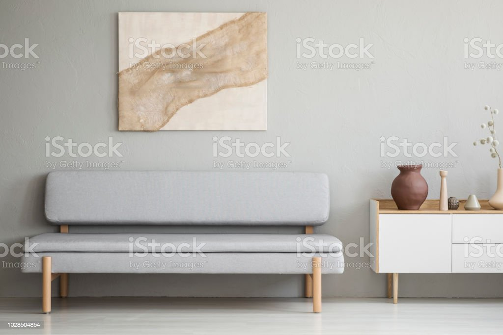 Poster above grey sofa next to white cupboard in simple living room interior. Real photo