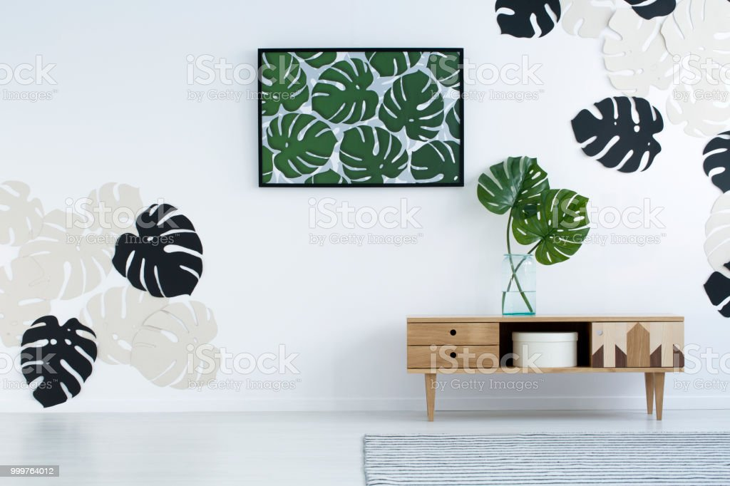 Poster and monstera leaves on wooden cupboard in modern white living room interior. Real photo