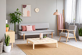 Poster and plant in living room interior with armchair next to grey sofa and wooden table. Real photo