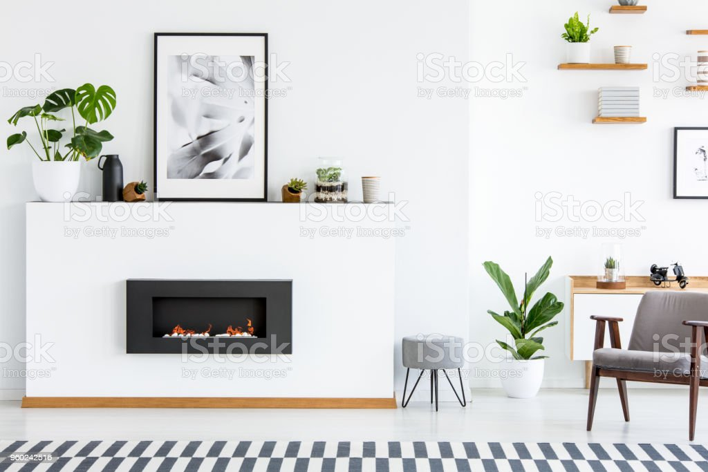 Poster and plant on white board with fireplace in cosy living room interior with armchair. Real photo stock photo