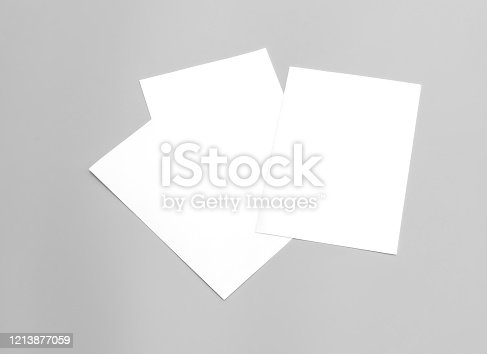932100364 istock photo Poster mock-ups paper, white paper isolated on gray background, Blank portrait paper A4. brochure magazine newspaper isolated on gray, can use banners products business texture background for your. 1213877059