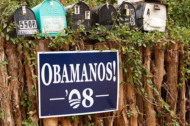 """""""OBAMANOS!"""" Poster on Traditional Coyote Fence, Santa Fe, NM Santa Fe, USA - October 12, 2008: An """"OBAMANOS! 08"""" poster on a traditional coyote fence under mailboxes in Santa Fe, NM. The slogan was a popular one among Spanish-speaking Obama supporters in the Southwest USA. barack obama stock pictures, royalty-free photos & images"""