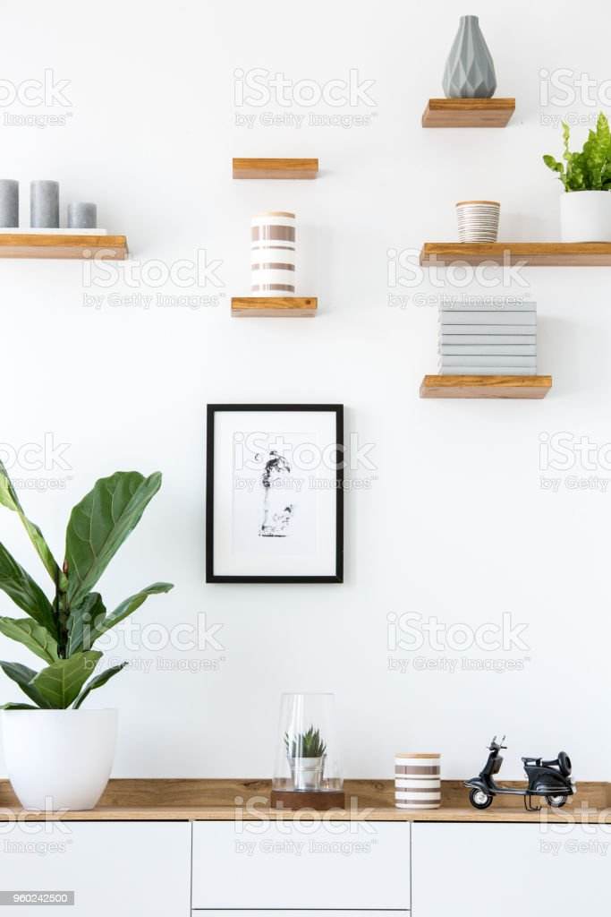 Poster on white wall above wooden cupboard with plant in simple interior. Real photo stock photo