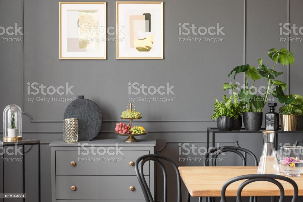 Posters boven grijs kabinet in donkere eetzaal interieur met