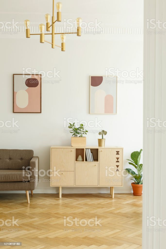 Posters On A White Wall Comfy Sofa And A Simple Wooden Cabinet In A Real Retro Living Room Interior With Herringbone Parquet Floor Stock Photo Download Image Now Istock