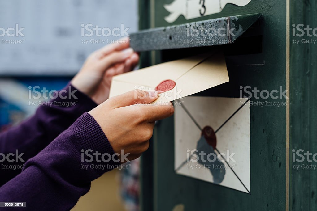 Posting letter to old postbox on street stock photo