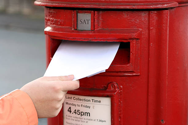 posting letter to red british postbox stock photo