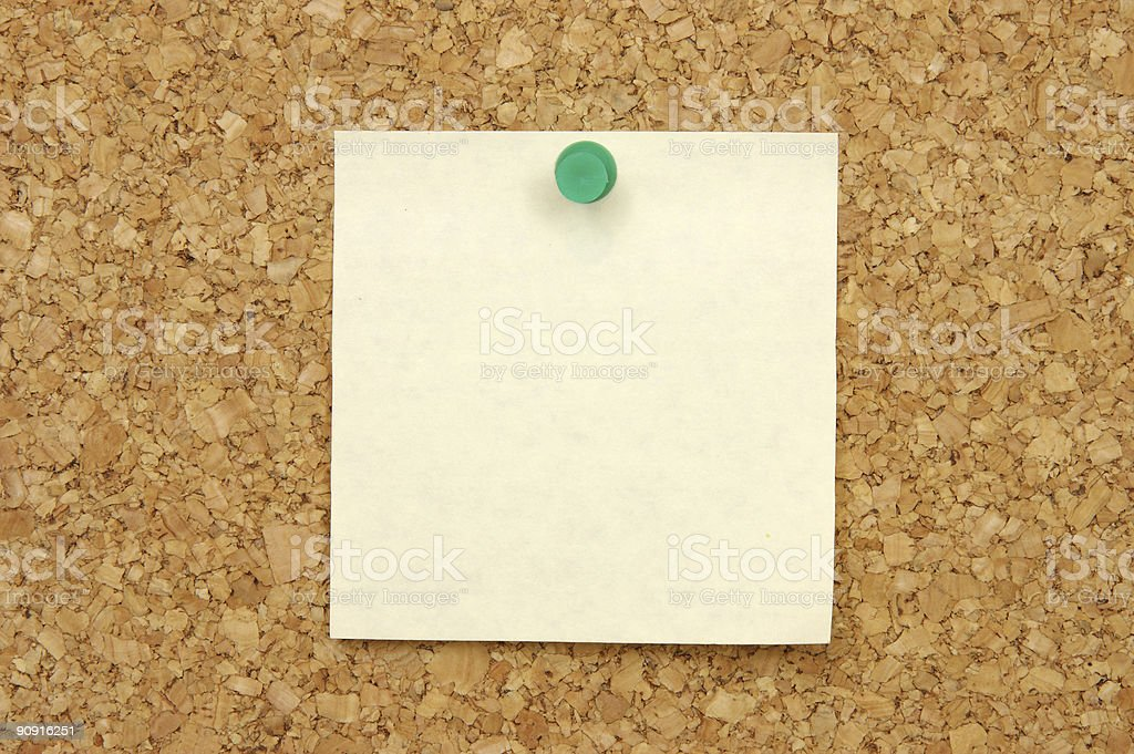 Post-it note with pushpin on corkboard stock photo