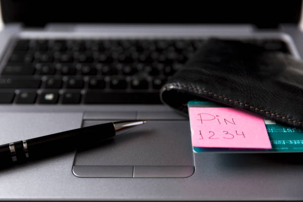 Post-it with credit card PIN number in wallet on laptop. Unsafe way to keep PIN number stock photo