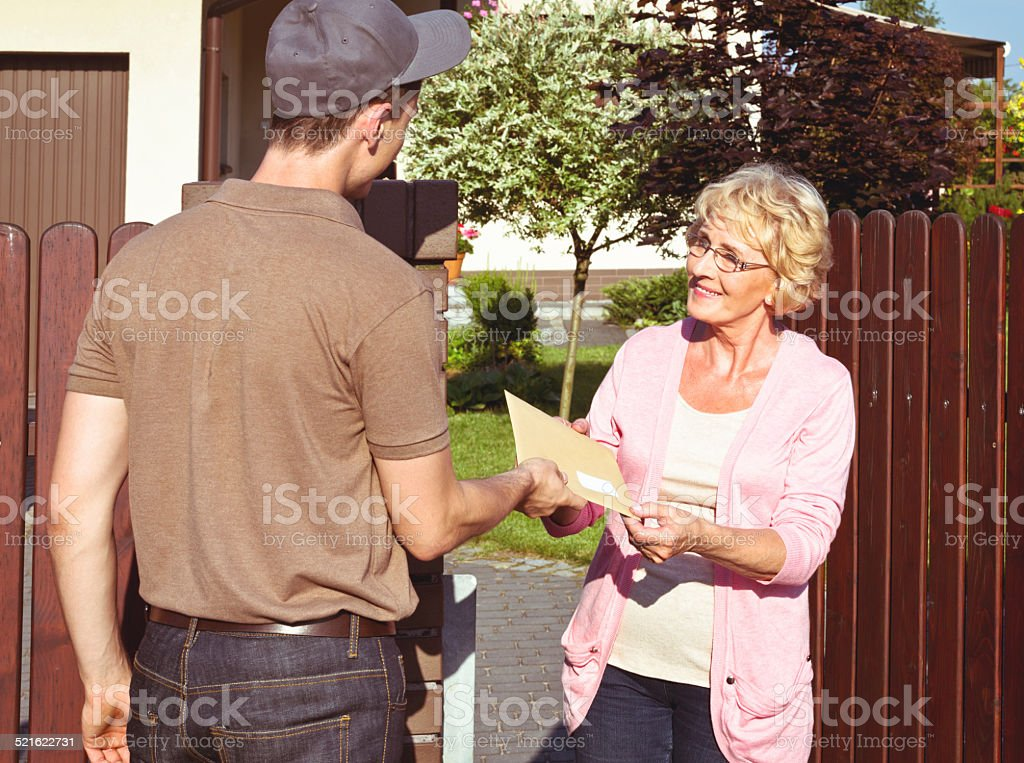 Postman delivering a letter for senior lady Happy senior woman standing outdoor in front of her house and receiving an envelope from young postman. 60-64 Years Stock Photo