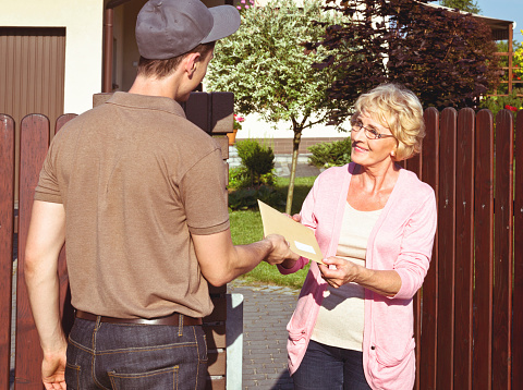 Postman Delivering A Letter For Senior Lady Stock Photo - Download Image Now