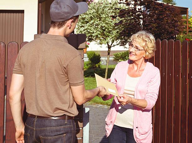 почтальон доставлять письмо для старших леди - postal worker стоковые фото и изображения
