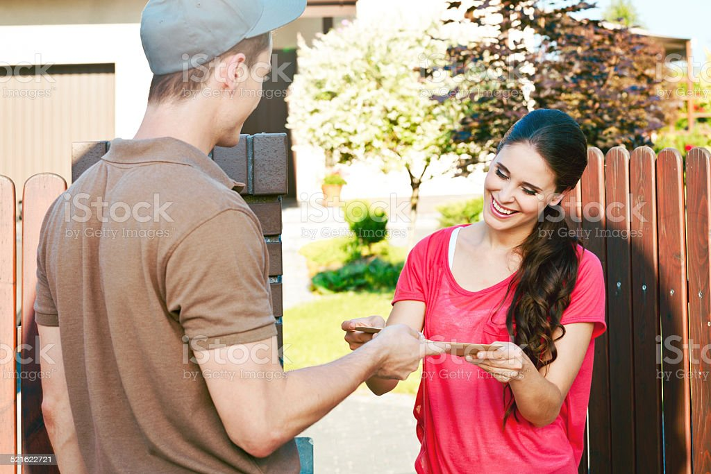 Postman delivering a letter for young woman Happy young woman standing outdoor in front of her house and receiving an envelope from young postman. 20-24 Years Stock Photo