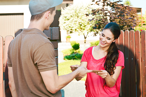 Postman Delivering A Letter For Young Woman Stock Photo - Download Image Now