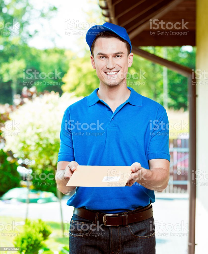 Postman delivering a mail Portrait of young postman standing outdoor, holding an envelope in hands and smiling at camera. 2015 Stock Photo